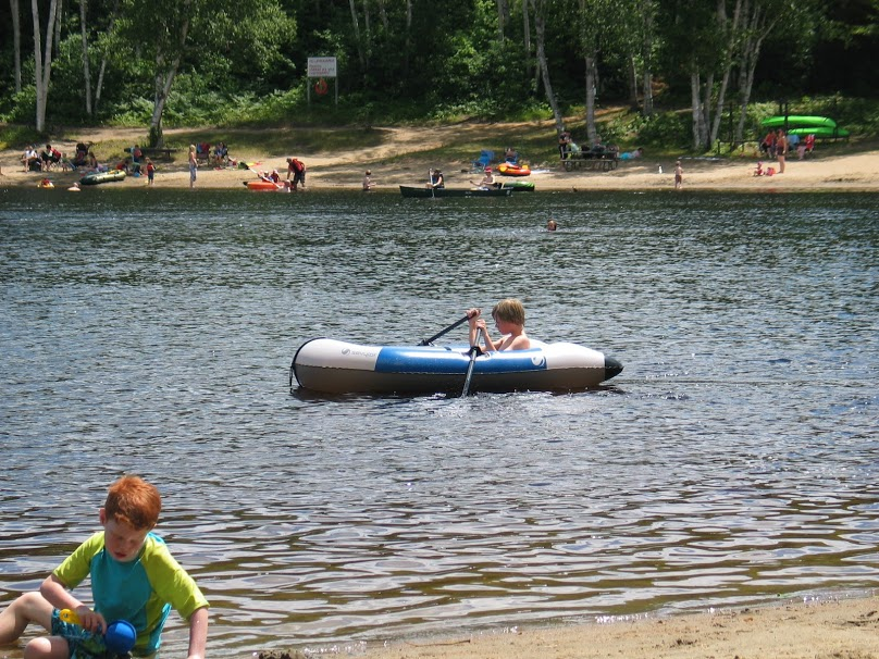 kids playing on the beach and in a boat at Arrowhead Lake