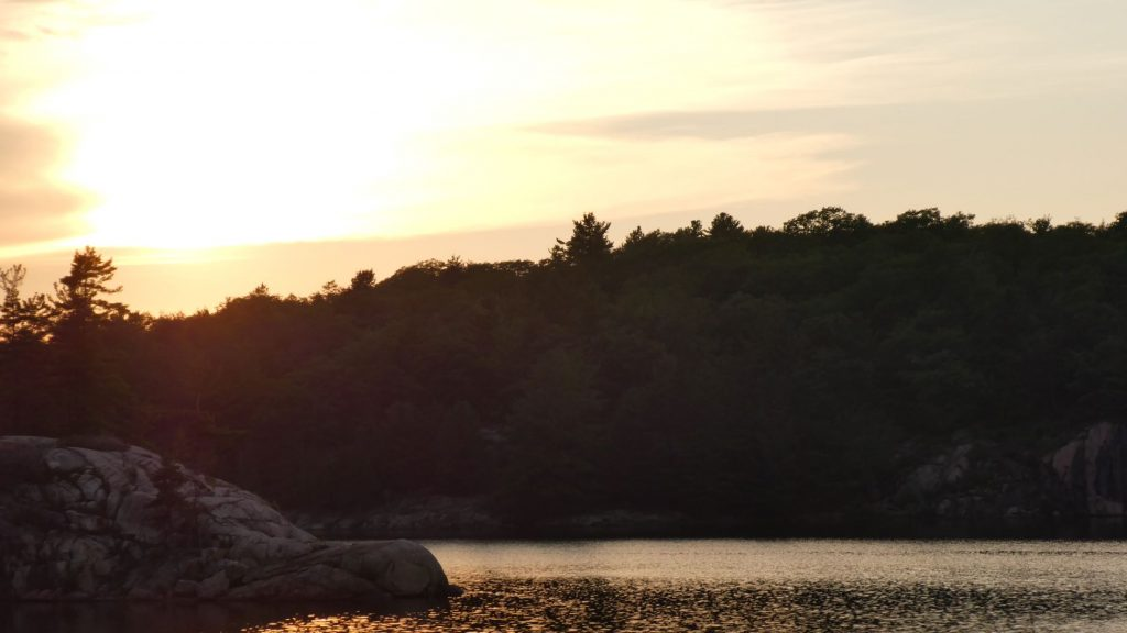 the sun setting above the rock outcropping that we dubbed the dolphin's nose at George Lake in Killarney Provincial Park