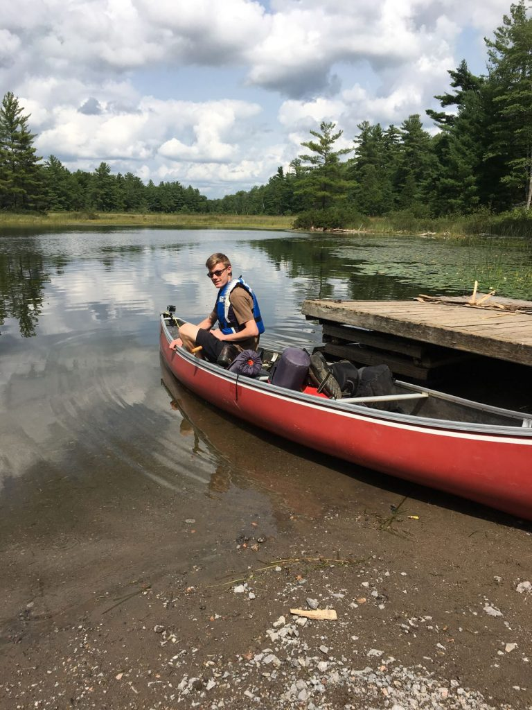picture of Thomas in our fiberglass canoe while backcountry camping at Kawartha Highlands Provincial Park