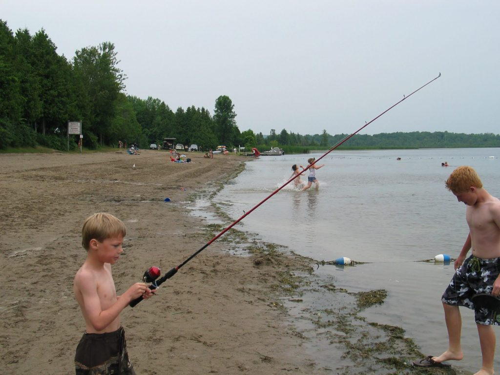 picture of a young boy with a fishing rod fishing on the beach at Emily Provincial Park