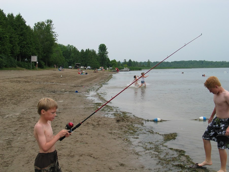 Picture of Thomas on beach fishing at Emily Provincial Park in the summer while camping.